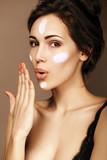 Sensual woman applying moisturizing cream on her face