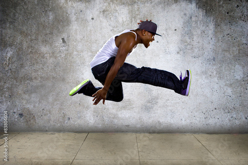 hip hop dancer jumping high on concrete Poster