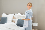 Fototapety Housekeeper Holding Stack Of Sheet