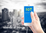 Hand holding smartphone with Internet of things (IoT) word with poster