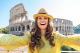 Smiling woman tourist taking selfie at Rome Colosseum