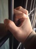 Mani di due innamorati tra le sbarre di una prigione