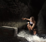 Woman traveler in sea cave with tresure chest poster
