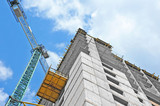 Crane and building construction site against blue sky - 84013239
