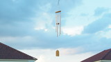 wind chime tube mobile in breeze, Home village background.  poster