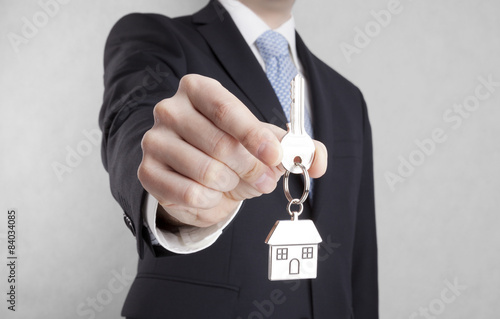 Poster House key in businessman hand with clipping path