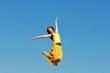 Постер, плакат: девушка в прыжке на фоне неба в желтом платье