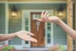 Mani con chiavi sfondo porta di casa