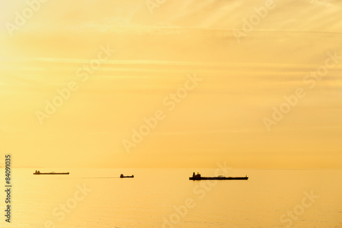 cargo ships at sunset with calm sea