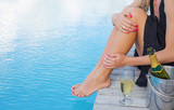 Lady sitting by the pool, focus on champagne glass