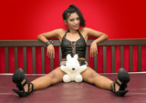 woman in black leather sitting on bed with teddy bear