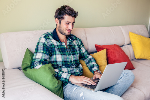 Poster Handsome young man sitting on couch working on his laptop