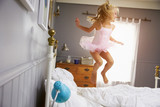Fototapety Girl In Ballerina Outfit Jumping On Parents Bed