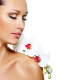 Fototapety Face of  beautiful woman with a white orchid flower