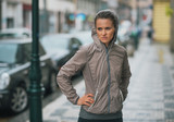 Woman runner wearing rain gear stopped and feeling unmotivated poster