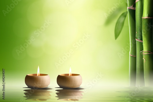 Zen concept. Two candles in bamboo forest.