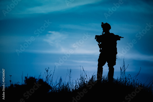 Poster Silhouette of military soldier or officer with weapons at night.