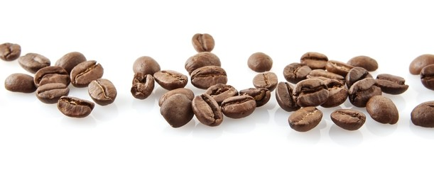 Scattered coffee beans in line on white
