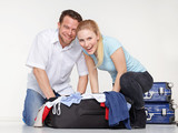 Couple packs overcrowded bag for holiday poster