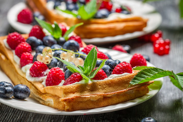 Closeup of waffels with cream, blueberry and raspberry