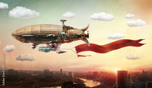 Dirigible with a banner, in the sky over a city.