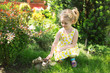 Portrait of a cute little girl in sunny summer day at green natu