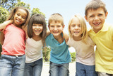 Group Of Smiling Children Relaxing In Park - 84417235