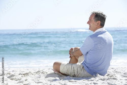 Senior Man On Holiday Sitting On Sandy Beach Poster