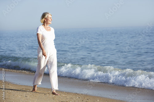 Senior Woman Enjoying Beach Holiday Poster