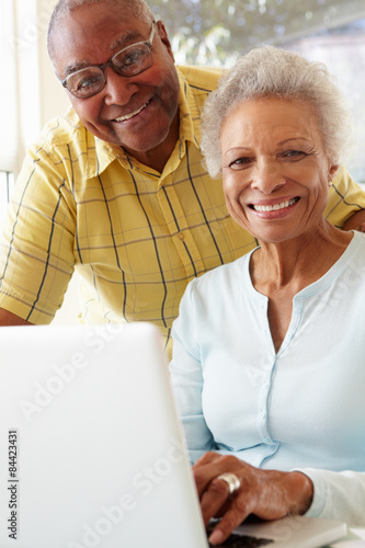 Senior Couple Using Laptop At Home Poster