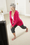 Senior Woman Exercising Whilst Watching Fitness DVD On Television