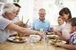Detaily fotografie rodina multi generace jíst jídlo kolem kuchyňského stolu