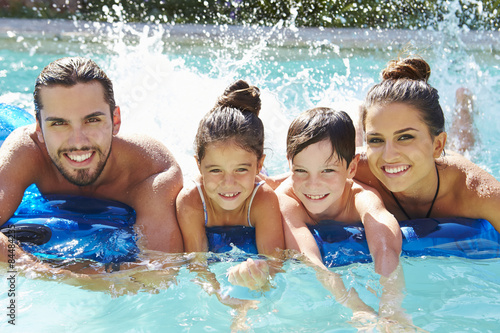 Portrait Of Family On Airbed In Swimming Pool Poster