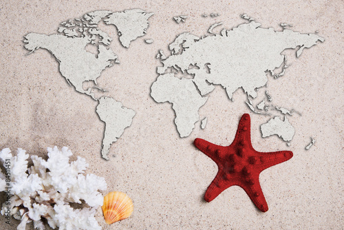 Map of the world. Traveling concept. Starfish with coral on the Beach sand