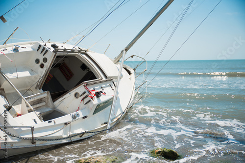 Papiers peints Naufrage sailboat wrecked and stranded on the beach