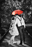 Young romantic couple in love flirting in rain. Red umbrella - 84612055