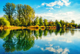 Fototapety Tranquil lakeshore landscape with blue sky and water