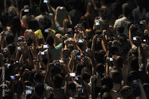 Excited youngsters attending a show, applauding and taking videos vith cell phones