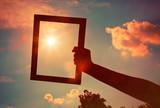 Hand holding a wooden frame on sunrise sky background. Care, saf poster