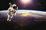 Astronaut in outer space above the earth during sunset. Elements - Fine Art prints