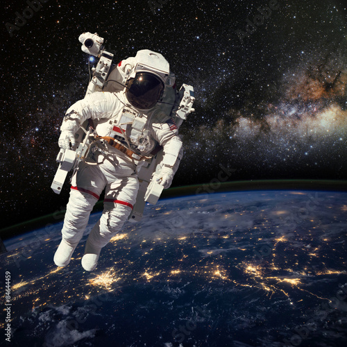 Plexiglas Astronaut in outer space above the earth during night time. Elem