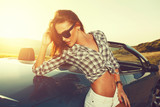 Attractive young woman posing leaning on convertible car