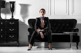 young beautiful woman sitting on sofa in minimalistic inteior - 84685213