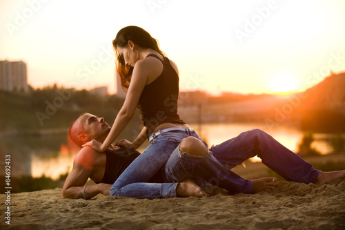 Couple in jeans on the beach, woman sitting like a horsewoman