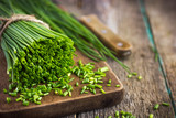 bunch of  chives on a wooden cutting board - 84744256