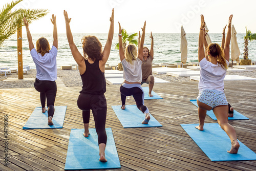 Poster group of young females practicing yoga on the seaside during the sunrisе