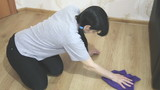 young brunette woman cleaning the floor with a cloth