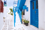 Streetview of Mykonos town with white street, stairs and blue door, Greece
