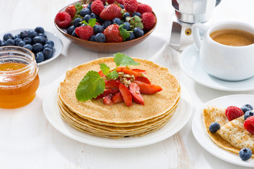 crepes with strawberry, jams and honey on white table