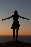Teenage girl standing silhoutted on the cliffs at sunset looking out to sea with her arms spread wide.